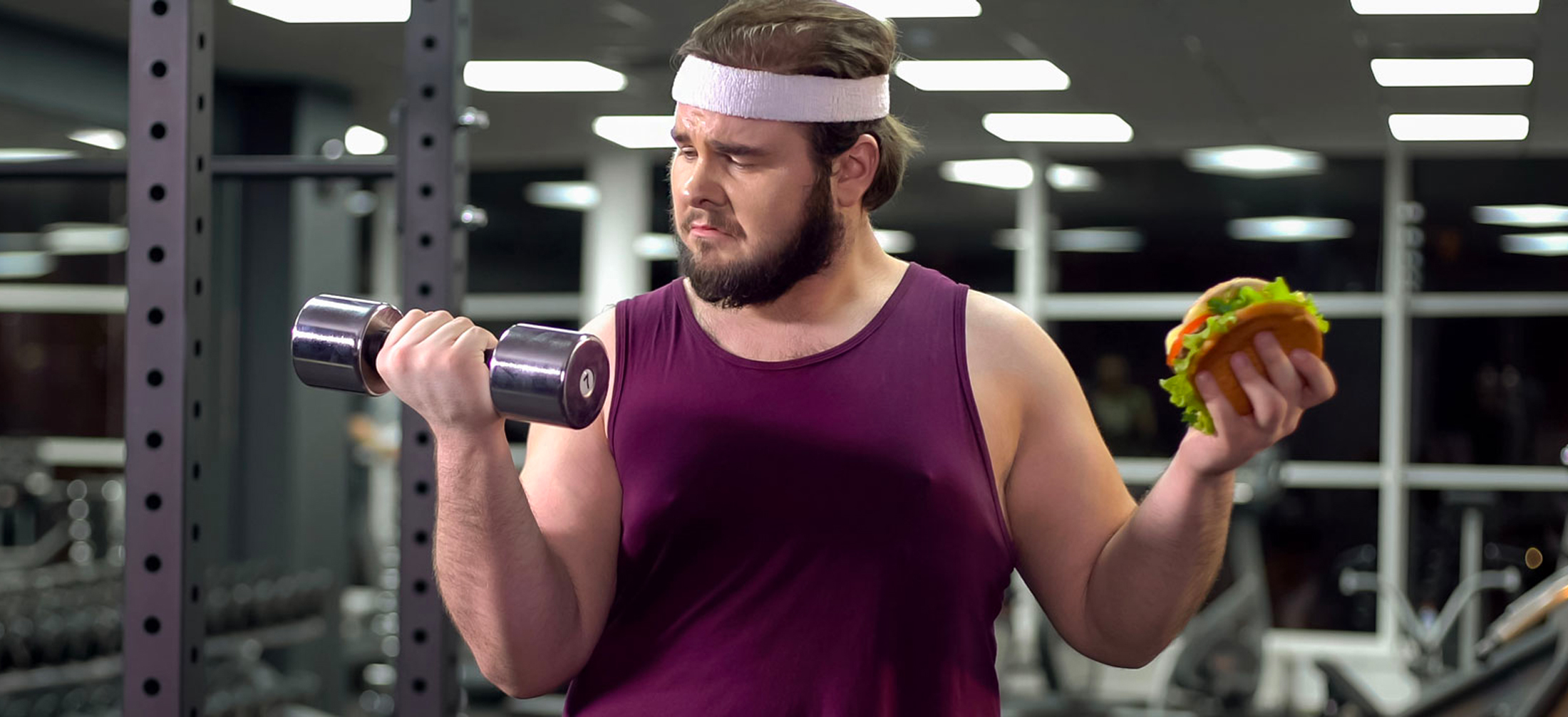 guy in gym holding weight and hamburger